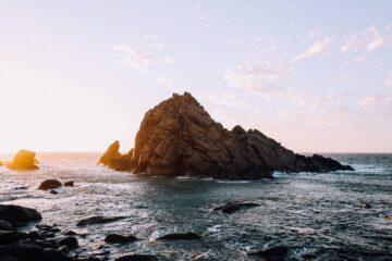wavy sea washing rocky formation under sundown sky